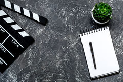 Work table of producer. Movie clapperboard and notebook on grey stone background top view copyspace Royalty Free Stock Image
