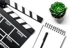 Work table of producer. Movie clapperboard and notebook on white background top view Royalty Free Stock Photos