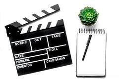 Work table of producer. Movie clapperboard and notebook on white background top view.  royalty free stock image