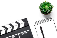 Work table of producer. Movie clapperboard and notebook on white background top view copyspace Royalty Free Stock Photo