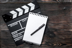 Work table of producer. Movie clapperboard and notebook on wooden table background top view copyspace Royalty Free Stock Photos