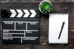 Work table of producer. Movie clapperboard and notebook on wooden table background top view Royalty Free Stock Image