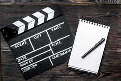 Work table of producer. Movie clapperboard and notebook on wooden table background top view Royalty Free Stock Photos