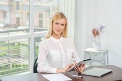 Work on the tablet. Blonde woman works for your tablet and looki Royalty Free Stock Photos