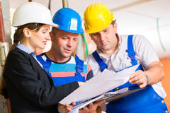 Work Team on construction site controlling floor plan. Construction site team or architect and builder or worker with helmets controlling or having discussion of Stock Photography