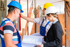 Work Team on construction site controlling floor plan Royalty Free Stock Image