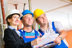 Work Team on construction site controlling floor plan Royalty Free Stock Photography