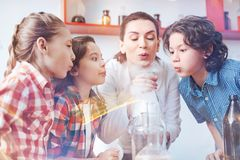 Children blowing on fuming laboratory flask at school Royalty Free Stock Photo
