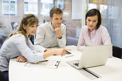 Work team in meeting room working on laptop Royalty Free Stock Image