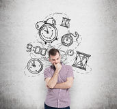 Work and timing. Young man with his ��� to the chin thinking about time, in two minds, several models of clocks drawn behind. A concept of a value royalty free stock photo