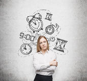 Work and timing. Young pretty businesswoman thinking about time, in two minds, several models of clocks drawn behind. A concept of a value of time in business stock photography
