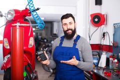 Work to repair the motorbike. Master counted the cost of the  professiona work to repair the motorbike in his workshop Royalty Free Stock Photo