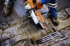 Work to update the road coverage.A circular saw cuts the pavement slabs. A circular saw cuts the pavement slabs. Work to update the road coverage Royalty Free Stock Photos