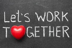 Work together. Let's work together phrase handwritten on blackboard with heart symbol instead of O Stock Photo