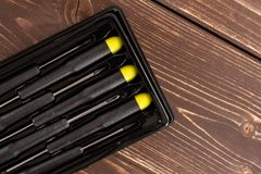 Work tool item on brown wood. Group of six whole screwdrivers with a yellow black plastic handle work item flatlay on brown wood royalty free stock images