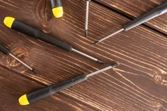 Work tool item on brown wood. Lot of whole screwdrivers with a yellow black plastic handle work item flatlay on brown wood stock images
