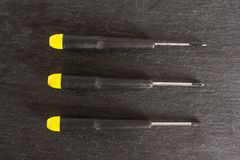 Work tool item on grey stone. Group of three whole screwdrivers with a yellow black plastic handle work item flatlay on grey stone stock image