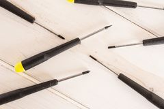 Work tool item on grey wood. Lot of whole screwdrivers with a yellow black plastic handle work item flatlay on white wood royalty free stock photos