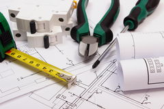 Work tools, electric fuse and rolls of diagrams on construction drawing of house Stock Images