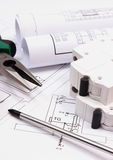 Work tools, electric fuse and rolls of diagrams on construction drawing of house Royalty Free Stock Images