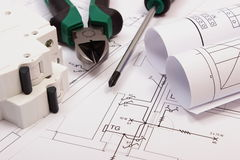 Work tools, electric fuse and rolls of diagrams on construction drawing of house Stock Photos