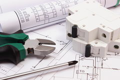 Work tools, electric fuse and rolls of diagrams on construction drawing of house Royalty Free Stock Photography