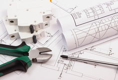 Work tools, electric fuse and rolls of diagrams on construction drawing of house stock photography