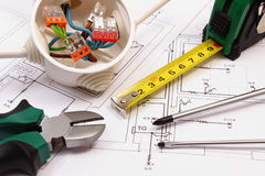 Work tools and electrical box with cables on construction drawing of house Royalty Free Stock Photo