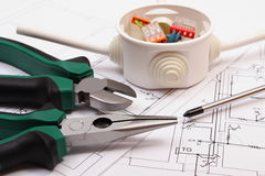 Work tools and electrical box with cables on construction drawing of house Royalty Free Stock Photography