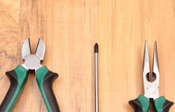 Work tools for engineer on wooden surface, technology. Metal pliers and electrical screwdriver on wooden surface, work tools and accessories for engineering jobs stock image