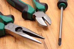 Work tools for engineer on wooden surface, technology. Metal pliers and electrical screwdriver on wooden surface, work tools and accessories for engineering jobs stock images