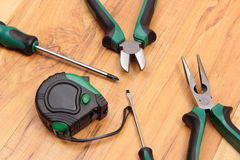 Work tools for engineer on wooden surface, technology. Metal pliers, electrical screwdrivers and tape measure on wooden surface, work tools and accessories for stock image