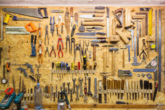 Work tools hanging on wall at workshop. Carpentry, woodwork and equipment concept - work tools hanging on wall at workshop Royalty Free Stock Photo