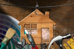 Work Tools and House - Home Improvement Concept. Home improvement concept - Wooden model house hanging on a steel cable with work tools Stock Photography