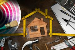 Work Tools and Model House - Home Improvement. Home improvement concept - Wooden model house with folding ruler, work tools and a calculator on a wooden desk royalty free stock images