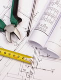 Work tools and rolls of diagrams on construction drawing of house Royalty Free Stock Images