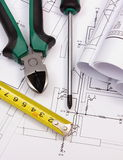 Work tools and rolls of diagrams on construction drawing of house Stock Images