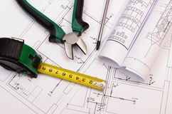 Work tools and rolls of diagrams on construction drawing of house Stock Photography