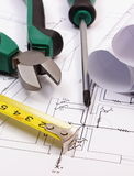 Work tools and rolls of diagrams on construction drawing of house Royalty Free Stock Photo