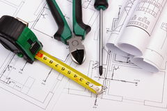 Work tools and rolls of diagrams on construction drawing of house Royalty Free Stock Photography