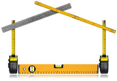 Work Tools in the Shape of a House. Tape measures, metal ruler, wooden folding ruler and a spirit level. Isolated on white background Royalty Free Stock Photos
