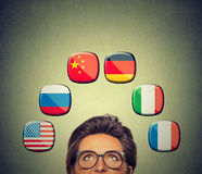 Work and travel opportunity concept. Woman in glasses looking up at icons of international flags. Work and travel opportunity concept. Foreign language studying Stock Photography