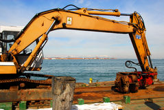 At work in Venice Lagoon. A backhoe loader in front of Murano Island Royalty Free Stock Image