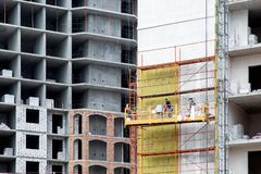 Work on weatherizing the facade of a high-rise building. Work on weatherizing the facade of a high-rise building with mineral wool for heat saving of a royalty free stock photo