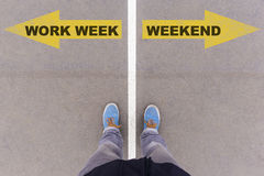 Work week vs weekend text arrows on asphalt ground, feet and sho Royalty Free Stock Photography