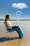 Work wherever you want.. Cloud computing: woman with laptop working at the beach Stock Photos