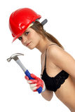 Work Woman. A young woman dressed in a black brassiere and red hard hat, holds up a hammer with her gloved hand Royalty Free Stock Image