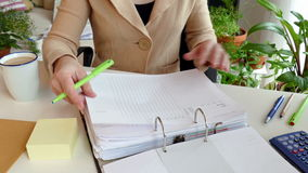 At work. A woman writes data to a list stock footage