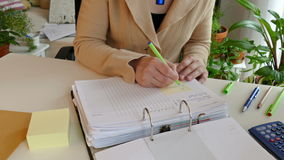 At work. A woman writes data to a list stock video footage