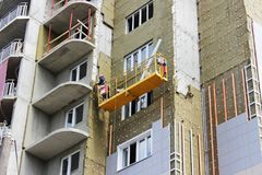 Work with yellow front suspended cradle on a newly built high-rise building.  stock images